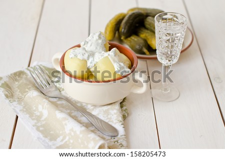 poor village dinner potatoes with sour cream and pickles - stock photo