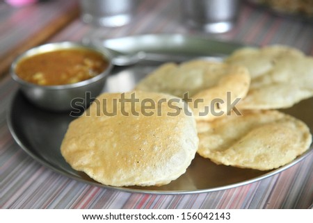 Poori or puri, also known as Indian fried bread, made from wheat flour dough. - stock photo