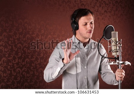 Pop singer singing a song in the recording Studio - stock photo