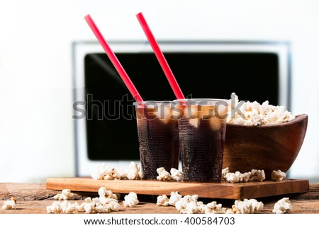 Popcorn and cola drink on wooden with TV background - stock photo