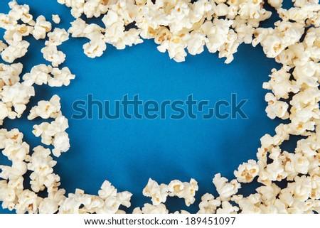 Popcorn border on blue background. - stock photo