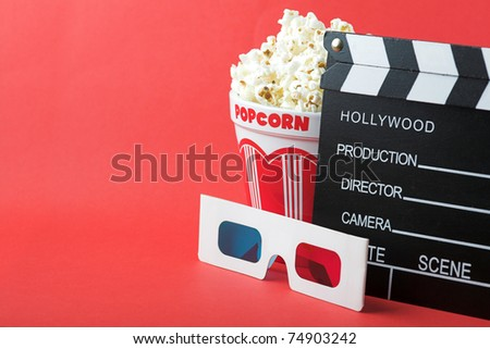Popcorn, 3D glasses & clapperboard on a red background - 3d cinema concept - stock photo