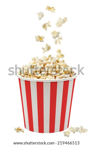 Popcorn falling in striped bucket on white background - stock photo