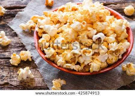 Popcorn in a bowl and scattered on a table close-up - stock photo