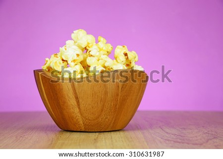 Popcorn in a wooden bowl on wood floor - stock photo