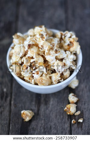 Popcorn in bowl with wooden background - stock photo