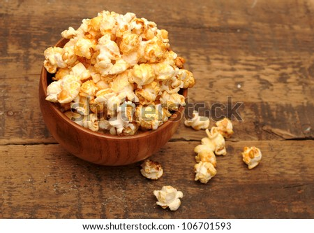 popcorn in brown bowl on wooden table - stock photo