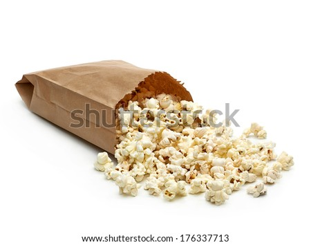 Popcorn in paper bag scattered on white background - stock photo