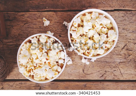 Popcorn in paper cups on wooden surface. Top view - stock photo