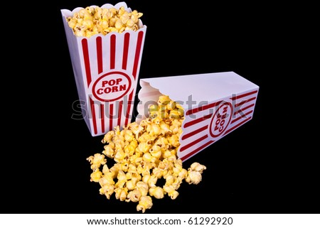 Popcorn in red and white containers with one spilled over on a black background. - stock photo