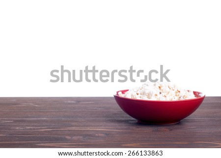 Popcorn in red plate on brown table side view background isolated - stock photo