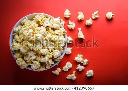 popcorn in white bowl on the red background, selective focus at popcorn in white bowl - stock photo