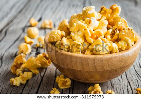 Popcorn in wooden bowl on wooden table background, selective focus, rustic style - stock photo