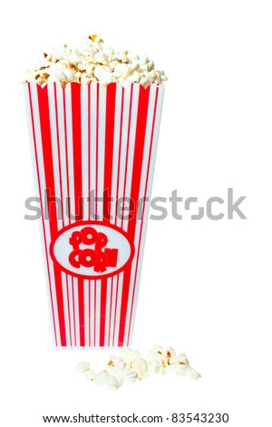 Popcorn tub overflowing with fresh delicious popcorn. Isolated on white - stock photo