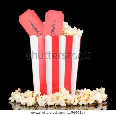 popcorn with cinema tickets isolated on black - stock photo