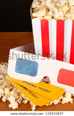 popcorn with tickets and cinema glasses on wooden table on brown background - stock photo