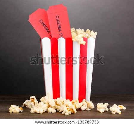 popcorn with tickets on wooden table on grey background - stock photo