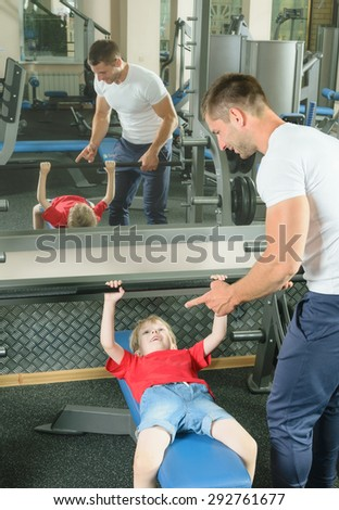 Pope shows little son how to lift weights in the gym - stock photo