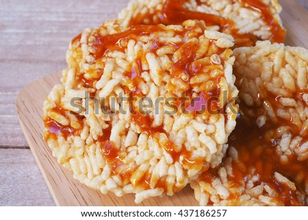 popped rice with molasses on a wooden table. - stock photo