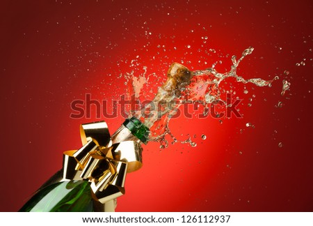 Popping cork from Champaign bottle with gold bow on it and splashes all around the red background - stock photo