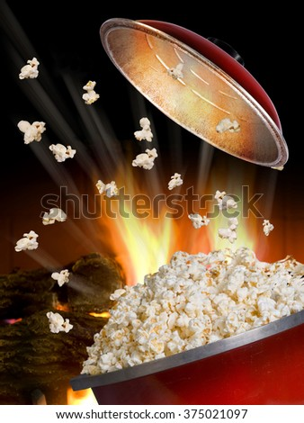 Popping popcorn the old fashion way in a red iron pot. - stock photo