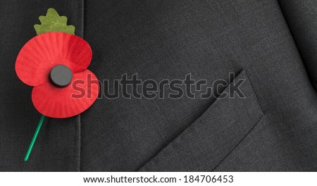 Poppy on jacket lapel for Remembrance and Armistice Day, for the world wars and symbol of peace. - stock photo