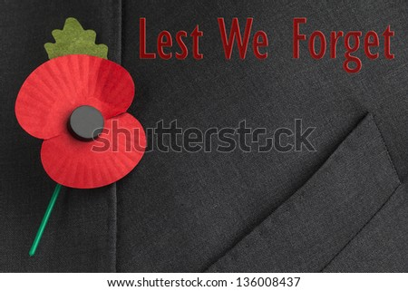 Poppy on jacket lapel for Remembrance Day - 'Lest We Forget'  - stock photo