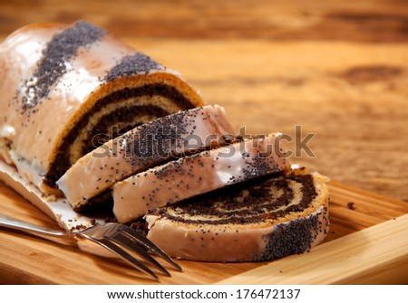 Poppy seed cake on wooden table  - stock photo