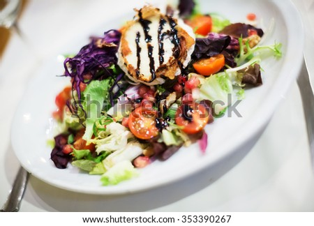 Popular Catalonian salad with cheese and dressing on white plate - stock photo