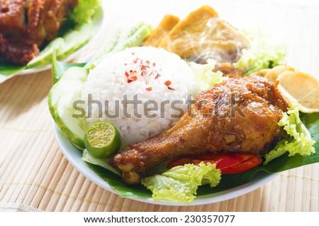Popular Indonesian local food nasi ayam penyet, indonesian fried chicken rice with sambal belacan. Fresh hot with steam smoke. - stock photo