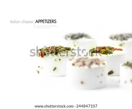Popular Italian soft cheese appetizer canapes with mixed toppings comprising of tomato, basil, olives and onion against a white background. Selective focus. Copy space. - stock photo