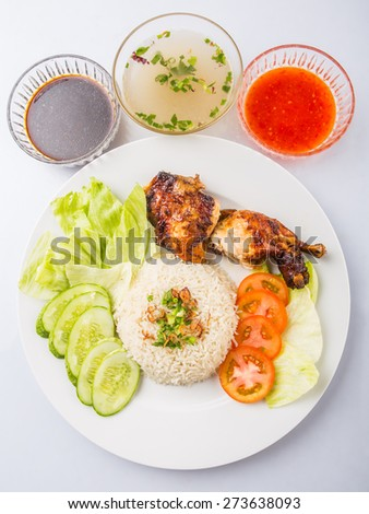 Popular Malaysian dish Nasi Ayam or chicken rice with baked chicken pieces, tomato, cucumber, salad, soup, soy sauce and chili sauce. - stock photo