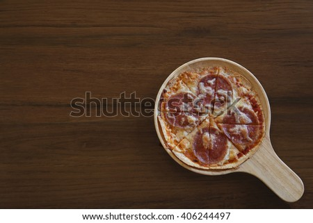Popular pizza on wooden table background. Top view with copy space - stock photo
