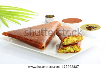Popular south indian breakfast masala dosa in golden brown color with 3 types of side dishes. - stock photo
