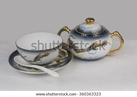 Porcelain cup and sugar bowl. White and blue porcelain Chinese. Gold blue dragons. - stock photo
