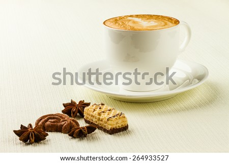 porcelain cup of cappucino, sweet and spices on white background - stock photo