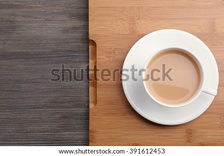 Porcelain cup of tea with milk on wooden tray, close up - stock photo