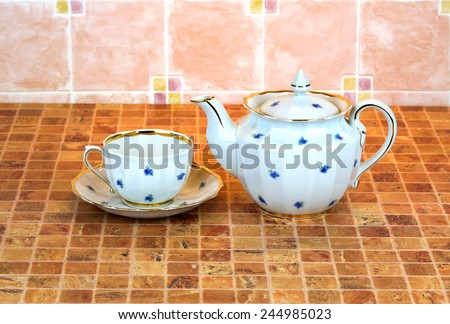 Porcelain Cup, saucer and teapot are in the multicolor table surface - stock photo