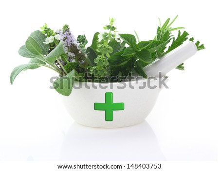 Porcelain mortar with pharmacy cross and fresh herbs - stock photo