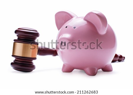 Porcelain pink piggy bank next to a wooden judge gavel, concept of savings, economic litigations and auctions, close-up with shadow on white - stock photo