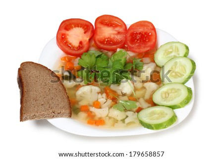 Porcelain plate with vegetable soup and bread on white background - stock photo