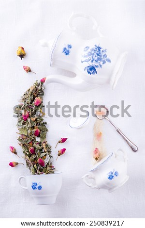 Porcelain sugar bowl with brown sugar and rose petals and magic antique teapot pouring tea from dry herbs in the teacup, Mad Hatter tea party - stock photo