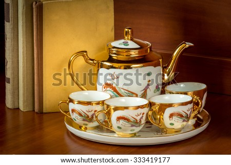 Porcelain teapot, teacup and saucer with dragon ornament in retro style - stock photo