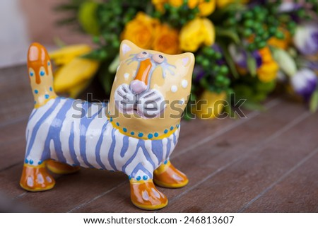 Porcelain tiger with bouquet of yellow roses on the background - stock photo