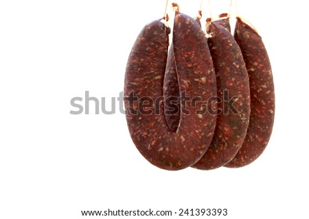 Pork and beef sausages hanged on hooks and waiting to get dry - stock photo