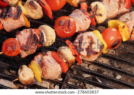 Pork And Vegetables Skewers Cooking On BBQ Grill. Good Lunch For Outdoor Summer Barbecue Party Or Picnic - stock photo