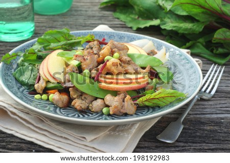 pork and vegetables stir fry with a fresh sliced apple - stock photo