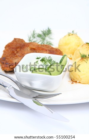 Pork chop (covered in batter and breadcrumbs), mashed potatoes and cucumber salad in a bowl decorated with dill on a plate with a fork and a knife on white background - stock photo