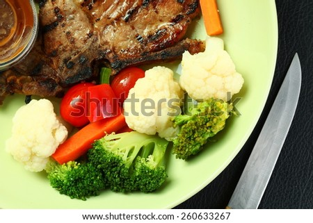 Pork chop steak and mixed vegetable ready to serve in the green plate represent the healthy food. - stock photo