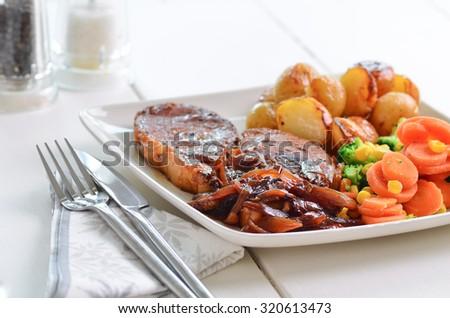 Pork chop Sunday lunch with onion gravy. - stock photo